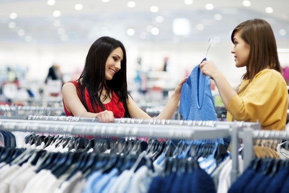 Two women next to a rack of clothing, picking out shirts.