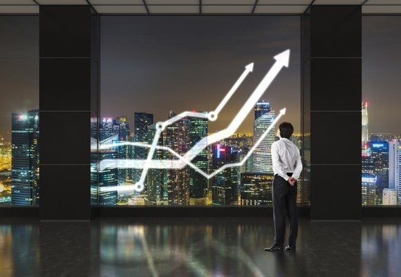 Man looking through skyscraper window at three line charts going up