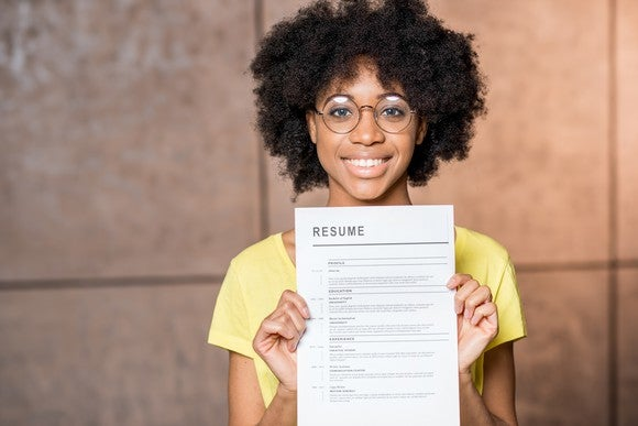 A young woman holds up her resume.