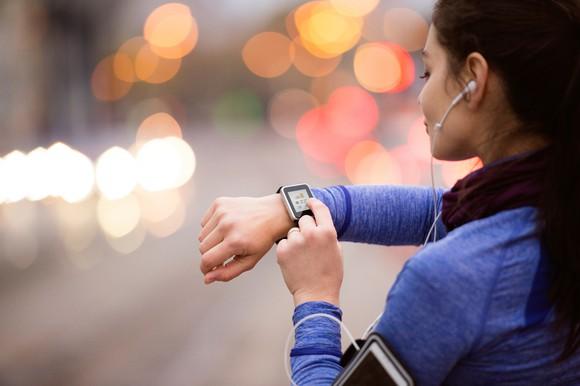 A jogger checks her fitness tracker.