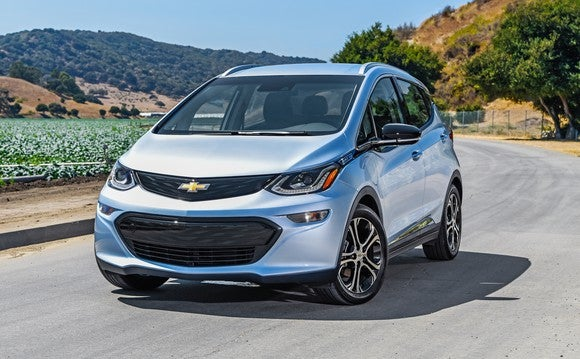 A light blue 2018 Chevrolet Bolt EV on a country road.