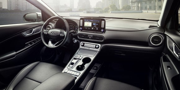 The dashboard and front seats of a Hyundai Kona Electric. The seats are leather-trimmed, and the interior panels are dark with chrome accents.
