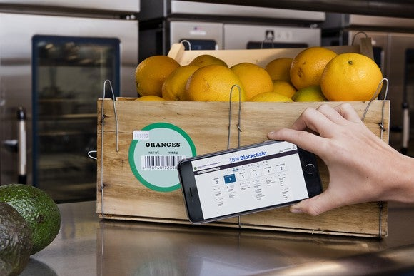 Smartphone using IBM Blockchain to track a crate of oranges.