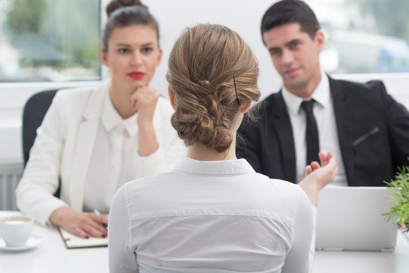 Three people in business dress sit across a table from each other.