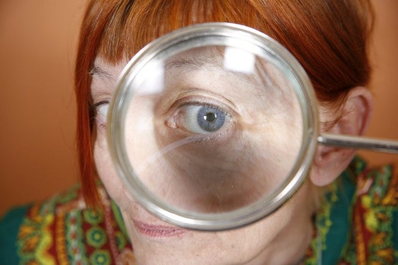 A senior woman stares through a magnifying glass.