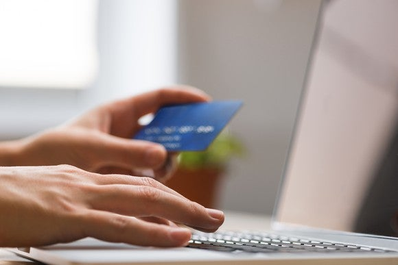 Hands holding credit card and typing on computer keyboard.