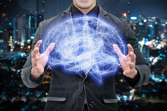 Man in suit with his hands cupping a large wire-frame, illuminated electronic brain.