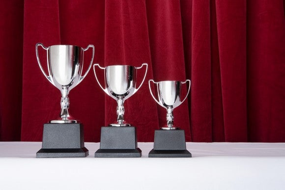 3 silver trophies of descending size, with a red curtain behind them.