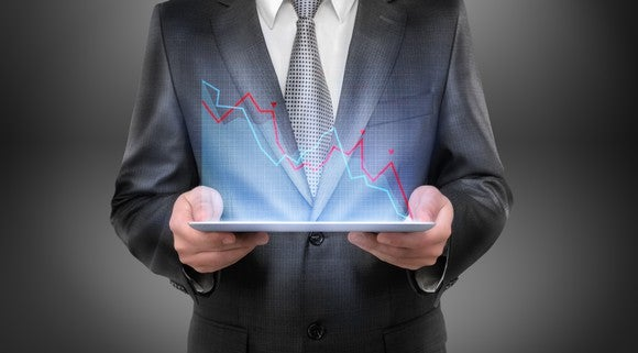 A man in a suit holds a digital financial chart with down pointing lines.