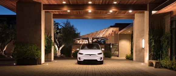 A white Model X with falcon wing doors open