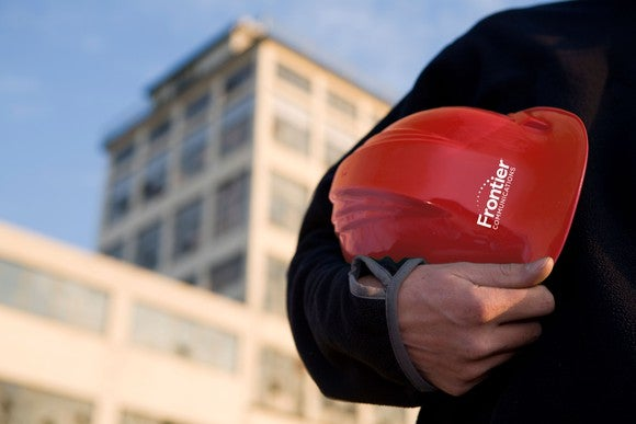 A Frontier worker holding a Frontier hardhat.