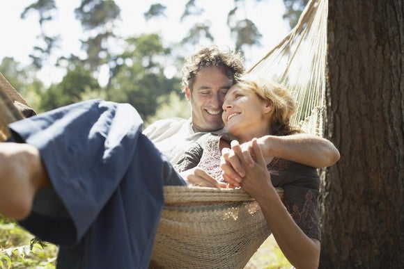 40-something couple relaxing in hammock.