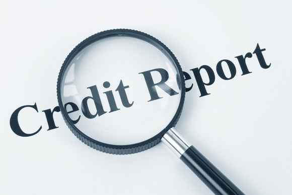 A magnifying glass hovers over the words credit report