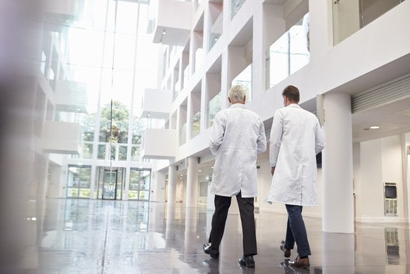 Two people in white lab coats walking through a hospital building atrium.