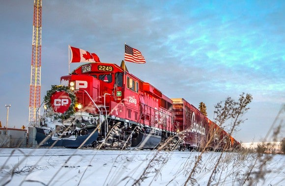 A red CP locomotive with the Canadian and U.S. flags on either side riding on a track with snow on the ground