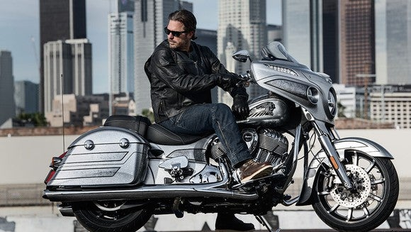 Rider on an Indian Motorcycle Limited Edition Chieftain Elite, with cityscape in background.