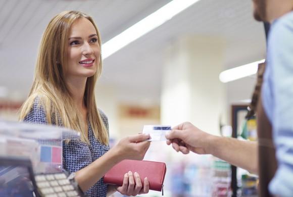 A woman hands a man her credit card.