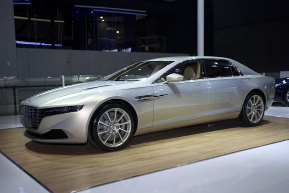 A 2015 Lagonda Taraf, a sleek luxury sedan, in silver on an auto-show display stand.