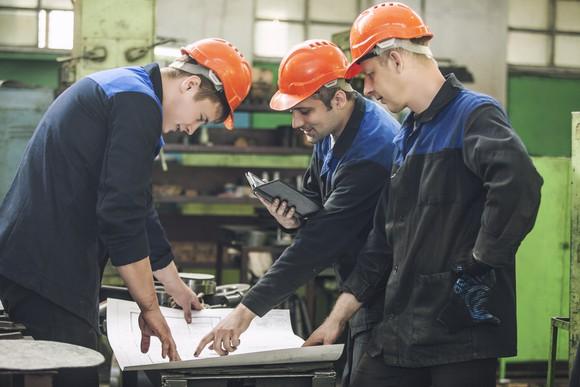 Three men in hard hats looking over construction blueprints