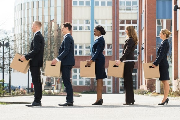 Five people, each carrying a cardboard box, standing in a line.
