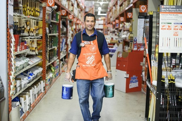 Home Depot associate carrying buckets of paint down a store aisle.