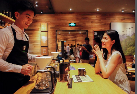 Smiling barista preparing coffee for a customer in a Chinese Starbucks.