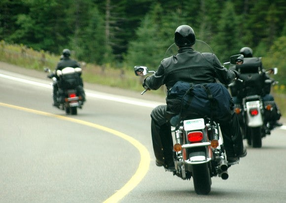 Three motorcycles being ridden by leather-clad men on the highway.