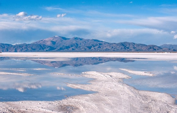Lithium-containing brine in an evaporation pond with mountains and blue sky in background.