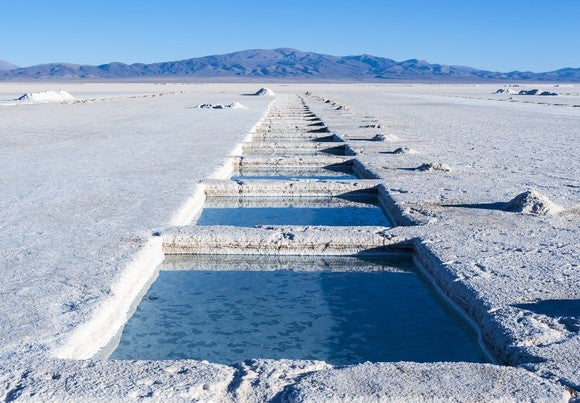 A lithium salt flat - shows brine evaporation pools wih mountains and blue sky in background.
