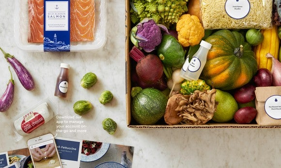 A package of salmon next to a box containing a Blue Apron meal kit with vegetables, dry noodles, and more inside