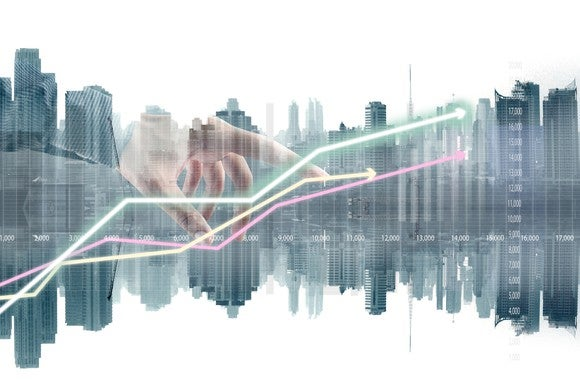 A hand plots a stock chart over a cityscape