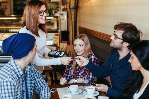 Man handing a credit card to a woman at a restarant