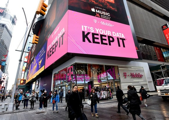 The outside of a T-Mobile store in Times Square, New York with people crossing the street in front of it.