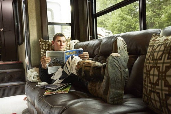 Person reading a magazine while sitting on couch in an RV.