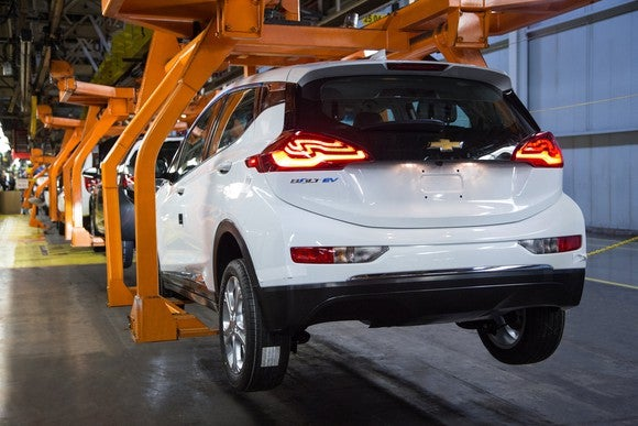 A partially assembled white Chevrolet Bolt EV is shown in an orange tooling cradle on an assembly line.