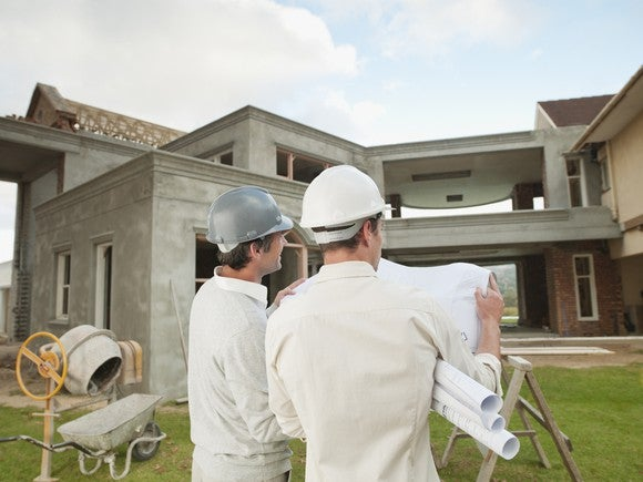 Two construction workers in hard hats facing a house while consulting house blueprints