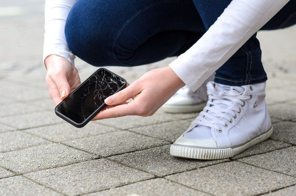Person holding a cracked phone after dropping it