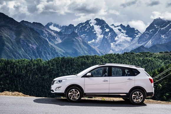 A white Baojun 560 SUV, with mountains in the background