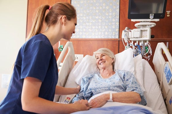 A nurse talking to a smiling senior female patient in a hospital bed.