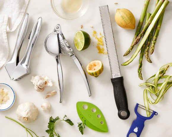 A mix of kitchen utensils and recipe ingredients spread over a counter