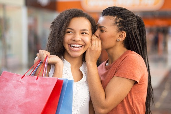 A woman whispers into into the ear of a smiling woman holding shopping bags