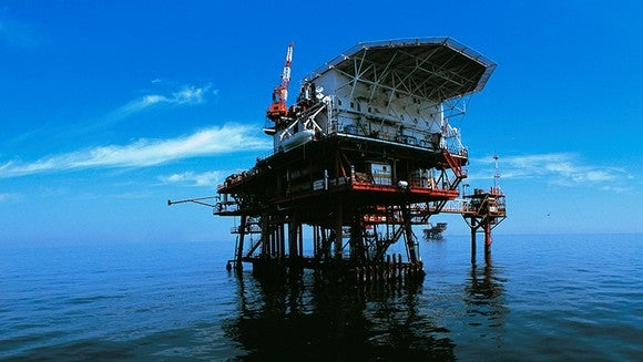 A drilling rig in the ocean with a blue sky in background.