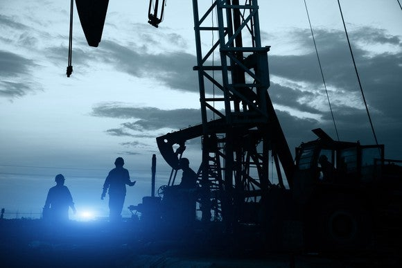 Silhouette of workers and an oil drill rig.