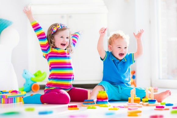 Two toddlers playing with toys and cheering