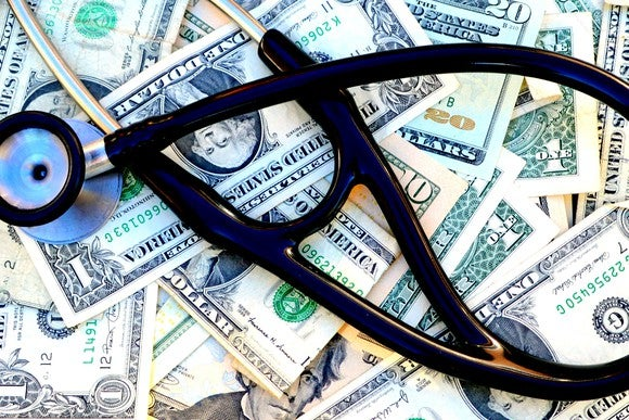 Dark blue stethoscope on top of dollar bills