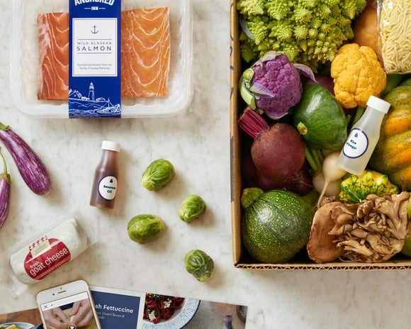 A Blue Apron box filled with various vegetables next to a package of salmon and goat cheese.