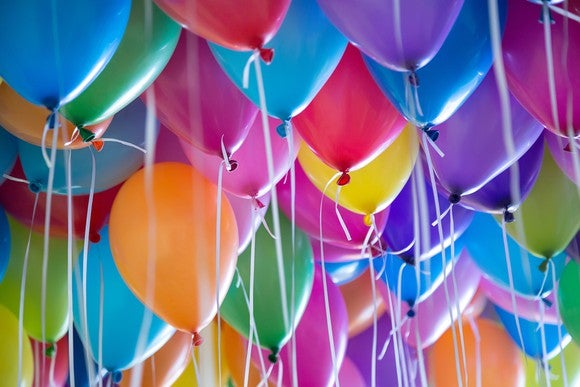 Many colorful balloons with strings tied to them