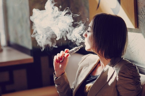 A woman smokes an e-cigarette.
