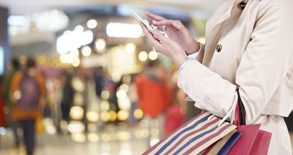 A woman uses her phone while walking in a mall.
