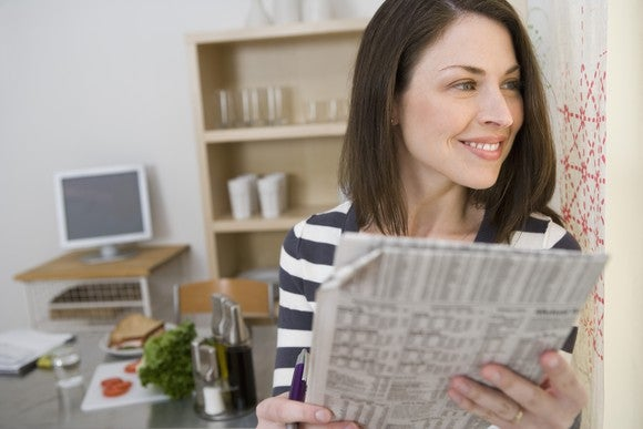A smiling woman reading the financial section of a newspaper.